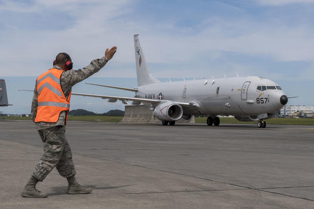 Staff Sgt. Duane Mitchell, 374th Maintenance Squadron transient alert maintenance craftsman, guides a Navy P-8A Poseidon aircraft into parking spot, Sept. 15, 2017, at Yokota Air Base, Japan. (U.S. Air Force photo/Airman 1st Class Donald Hudson)