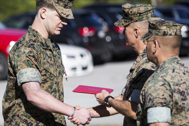 "Maj. Gen. Carl E. Mundy III awards the Bronze Star medal with Combat ""V"" to Staff Sgt. Patrick H. Maloney, multi-purpose canine handler with 2nd Marine Raider Battalion, at Camp Lejeune, N.C., on Oct. 30, 2017. Sgt. Salvador R. Moreno/Marine Corps"