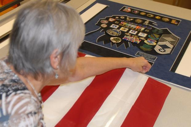 Janice Ethridge, Robins Air Force Base Frame Shop manager, folds a full-size flag into a shadow box display. (U.S. Air Force/Jonathan Bell)