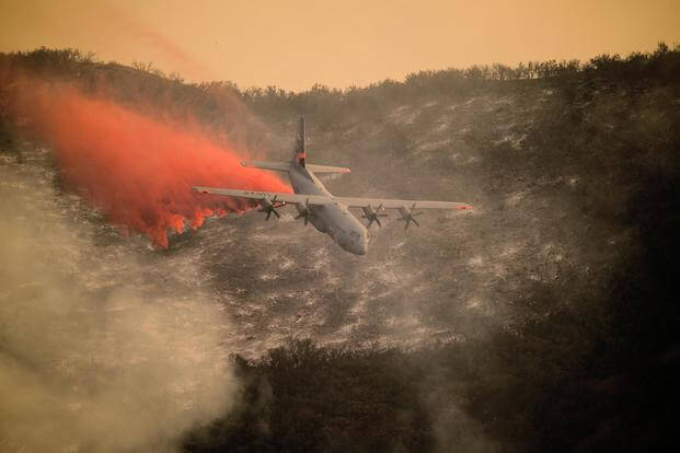 A U.S. Air National Guard C-130J Hercules aircraft equipped with the MAFFS 2 drops a line of fire retardant on the Thomas Fire in the hills above the city of Santa Barbara, California, Dec. 13, 2017. (U.S. Air National Guard/Staff Sgt. Nieko Carzis)