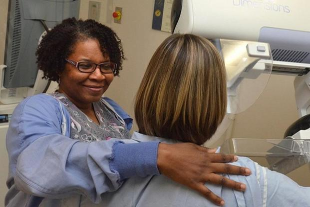 A radiologic technologist prepares a patient for a mammogram. (U.S. Navy photo)
