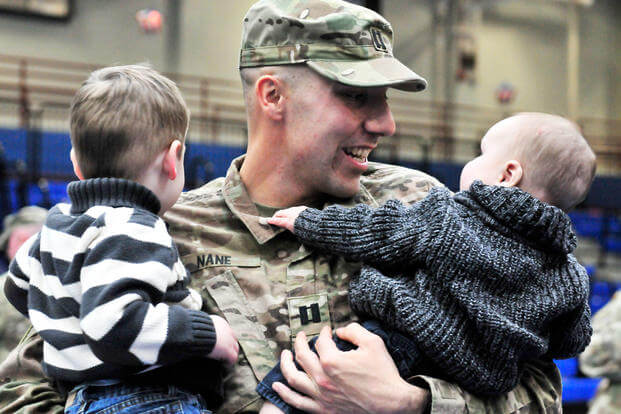 Cpt. Sebastiano Nane of the 548th Combat Sustainment Support Battalion holds his sons Luca (left) and Caleb (right) after a redeployment ceremony at Fort Drum's Magrath gym on December 18, 2017. (U.S. Army photo/ Liane Hatch)