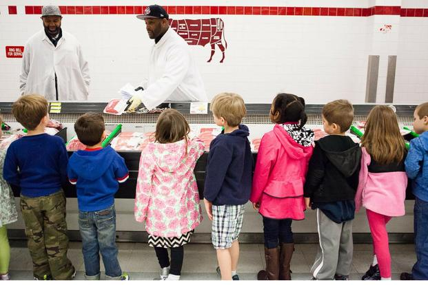 Damian Lofton, work leader, shows children from Cody Child Development Center's Robins B class of 4-to 5-year-olds packaged ground beef during a tour of Joint Base Myer-Henderson Hall's commissary. (U.S. Army/Rachel Larue)