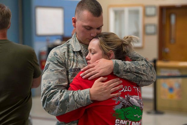 Senior Airman Nathan Slocum says his final goodbyes to a family member before deploying in support of Operation Freedom's Sentinel. (U.S. Air National Guard/Adam Juchniewicz)