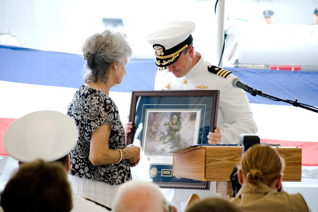 "Dolia Gonzalez, mother of Sgt. Alfredo ""Freddy"" Gonzalez, receives a portrait of her son during a change-of-command ceremony for the USS Gonzalez. (DoD photo)"