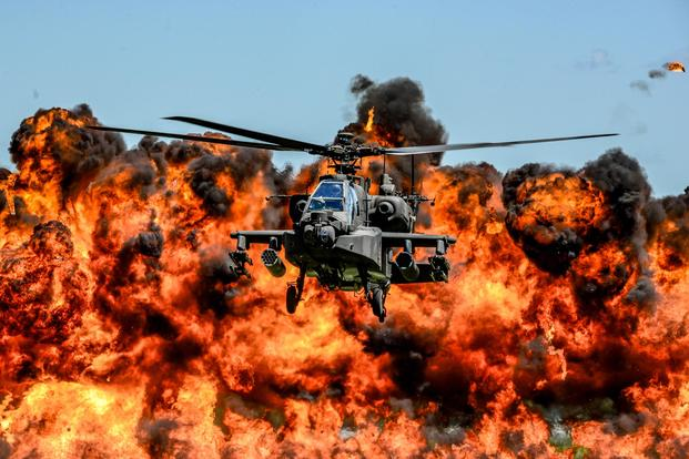 A U.S. Army AH-64D Apache Attack Helicopter, assigned to the 1-151st Attack Reconnaissance Battalion, flies in front of a wall of fire during the South Carolina National Guard Air and Ground Expo at McEntire Joint National Guard Base, South Carolina, May 6, 2017. (U.S. Air National Guard/Tech. Sgt. Jorge Intriago)