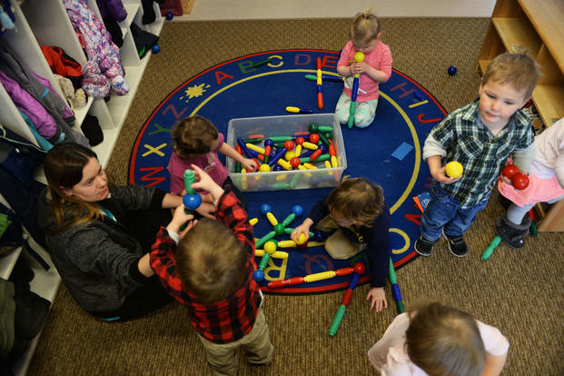 Crystal Emmons, a program technician at the McRaven Child Development Center, plays with the children in her classroom at Ellsworth Air Force Base, South Dakota. (U.S. Air Force/Thomas Karol)