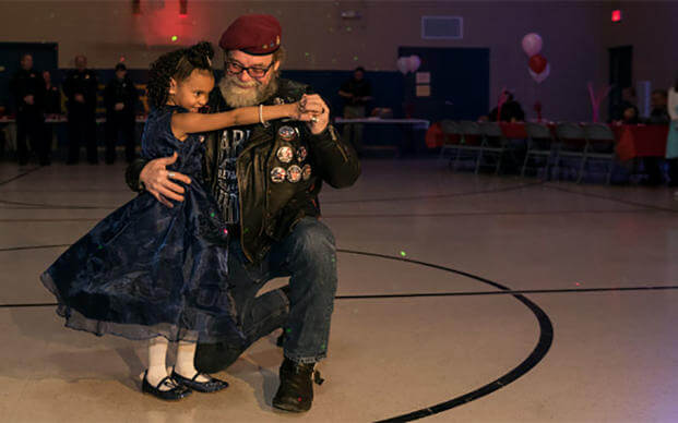 Cayleigh Hinton whose father, Sgt. Terrence Hinton died in a 2017 training accident, dances with David Gier, Senior Ride Captain of the Illinois Patriot Guard, at a father-daughter dance. (Illinois National Guard/Staff Sgt. Robert R. Adams)