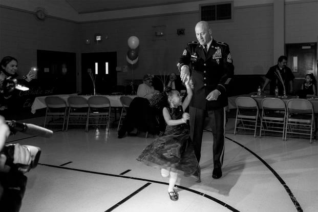Cayleigh Hinton, daughter of Sgt. Terrence Hinton, dances with 1st Sgt. Joseph Bierbrodt at a father-daughter dance in Illinois. Cayleigh's father, Sgt. Terrence Hinton, died in a training accident May 14, 2017 in Hawaii. (Illinois National Guard/Staff Sgt. Robert R. Adams)