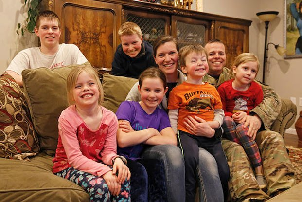 Maj. Patrick Vankirk sits with his wife Theresa, and their six children near Fort Drum, New York (U.S. Army/Paige Behringer)