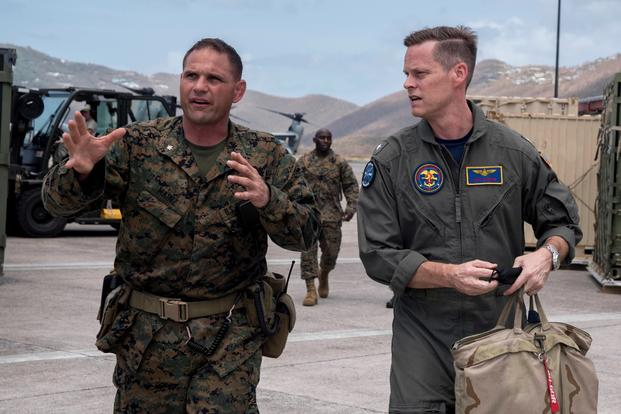 Rear Adm. Jeff Hughes, commander of Expeditionary Strike Group 2 (ESG-2), right, talks with Marine Lt. Col. Marcus Mainz, 26th Marine Expeditionary Unit (26th MEU) forward officer in charge, while both were embarked aboard the amphibious assault ship USS Kearsarge in September 2017 during relief efforts in the aftermath of Hurricane Irma. Mainz was relieved of command today. (Kaitlyn E. Eads/Navy)