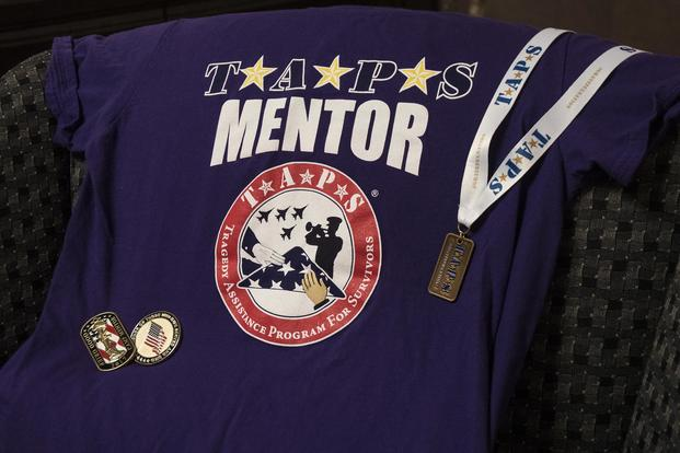 Air Force Capt. Nathaniel Lee has attended several Tragedy Assistance Program for Survivors camps and conferences since entering the program as a child, and now as a mentor. He has collected memorabilia to commemorate several visits and wears the purple TAPS shirt to symbolize his legacy role in the program. (U.S. Air Force photo by 2nd Lt. Scarlett Rodriguez)
