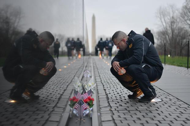 Master-at-Arms 1st Class Ian Barton reads a note left at the Vietnam Veterans Memorial during a run at the National Mall, April 9, 2018. (U.S. Navy photo/Stephen Hickok)