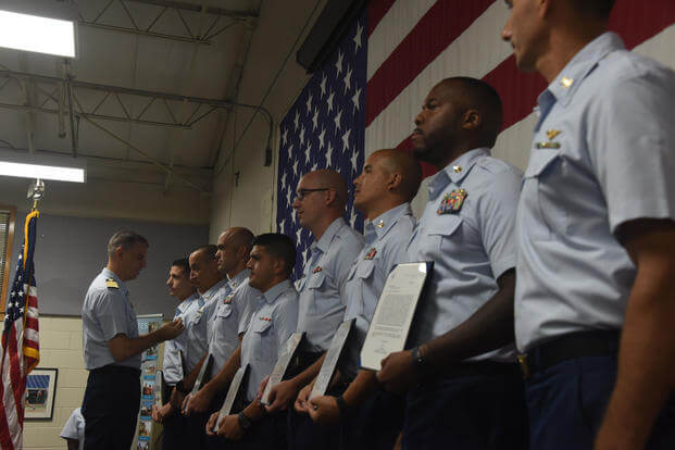 Capt. Ward Sandlin, commanding officer of Air Station Clearwater, Florida, pins on awards to members of the air station during an awards ceremony in Clearwater, July, 3, 2018. More than 100 awards were presented to Air Station Clearwater crewmembers for their efforts during the 2017 hurricane season. (U.S. Coast Guard photo/Ashley J. Johnson)