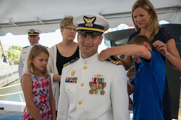 2c162922 Lt. Cmdr. Brendan Harris receives new shoulder boards from his children  during a promotion