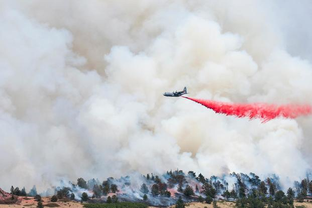 A C-130 Hercules equipped with a Modular Airborne Fire Fighting Systems drops slurry on the Spring Fire near Fort Garland, Colorado, July 4, 2018. (U.S. Army National Guard/Sgt 1st Class Marc Belo)