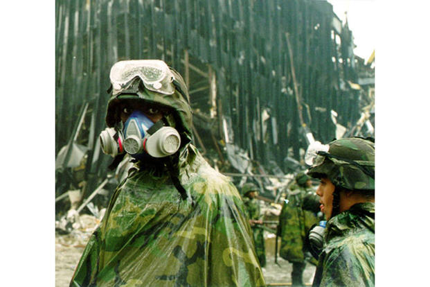 "Wearing a gas mask, a New York National Guard soldier from the ""Fighting"" 69th Infantry Division pauses amid the rubble at ground zero. (New York National Guard)"