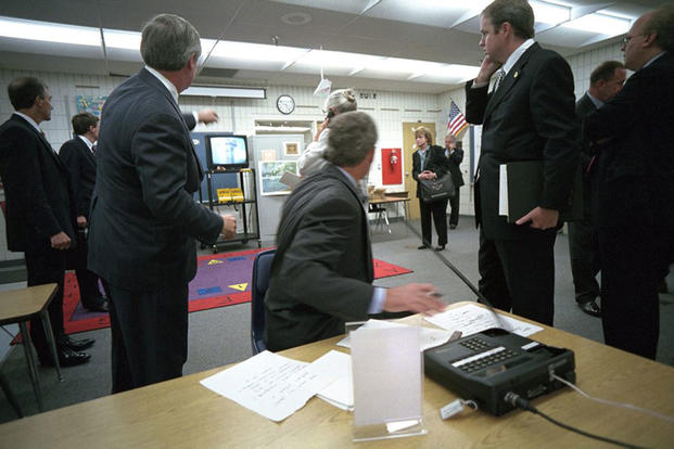 President George W. Bush turns around to watch television coverage of the attacks on the World Trade Center Tuesday, Sept. 11, 2001, as he is briefed in a classroom at Emma E. Booker Elementary School in Sarasota, Florida. (Photo by Eric Draper, courtesy of the George W. Bush Presidential Library)