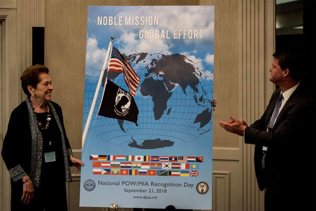 The 2018 National POW/MIA Recognition Day poster is revealed during the Annual National League of Families meeting in Crystal City, Virginia on June 21. The poster was unveiled by Ann Mills- Griffiths, Chairman of the Board and CEO of the National League of POW/MIA Families, left, and Randall G. Schriver, Assistant Secretary of Defense for Asian and Pacific Security. (US Marine Corps photo/Lauren Gramley)