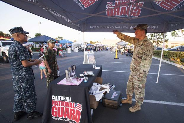 U.S. Army Master Sgt. Young Lee, a section chief with the California Army National Guard's Recruiting and Retention Command, talks with youth program cadets on Aug. 7, 2018, during National Night Out in Seal Beach, California. National Night Out is a nationwide event held at locations across the country to bring communities together with their local first responders and community-based organizations. (U.S. Air National Guard photo by Senior Airman Crystal Housman)