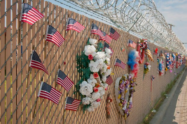 American flags, flowers, and photographs pay tribute to the 13 victims murdered in the Nov. 5, 2009, Fort Hood shootings Aug. 19, 2013. The items adorn the fence that surrounds the former Soldier Readiness Processing Center where the tragedy took place. (U.S. Army photo/Ken Scar)