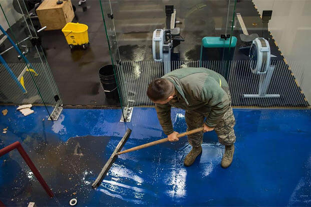 An airman at Joint Base Elemendorf-Richardson sweeps water at the base's Buckner Fitness Center a day after a 7.0 earthquake rattled the region. (U.S. Air Force)