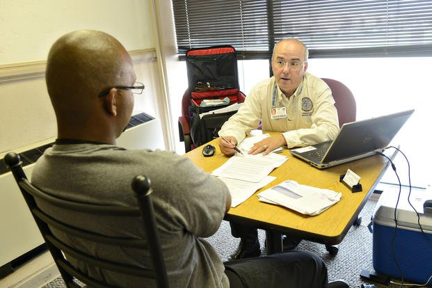 Randy Reynolds, a veteran service representative with the Oklahoma Department of Veterans Affairs Claims and Benefits Division, speaks with a veteran. (Air Force/Kelly White)
