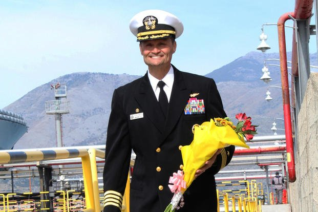 Capt. Kavon Hakimzadeh carries a bouquet of flowers for his wife following the USS Mount Whitney's arrival at its forward-deployed port of Gaeta, Italy Oct. 27, 2017. (U.S Navy photo/Rebeca Gibson)