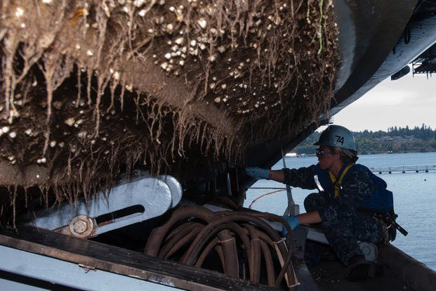 Seaman scrapes barnacles from bottom of rigid hull inflatable boat