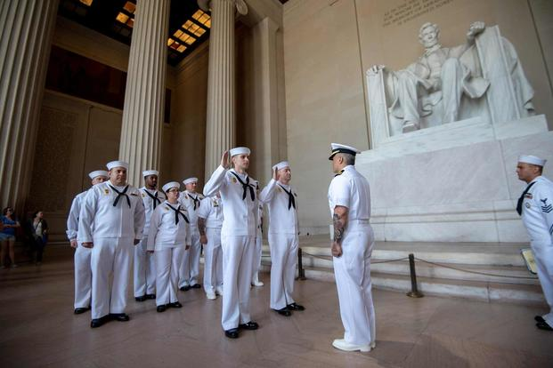 Sailors recite the oath of enlistment during their reenlistment ceremony.