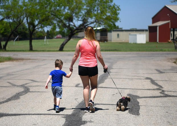 mother and son walking dog