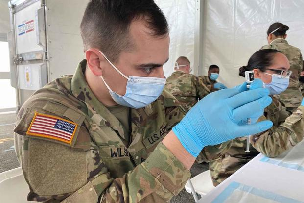 Soldiers fill syringes with COVID-19 vaccine.
