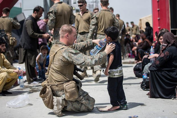 U.S. Marine Corps Marines from the 24th Marine Expeditionary Unit and U.S. Navy Corpsmen with Special Purpose MAGTF - Crisis Response - Central Command provide fresh water to children at Hamid Karzai International Airport in Kabul, Afghanistan.