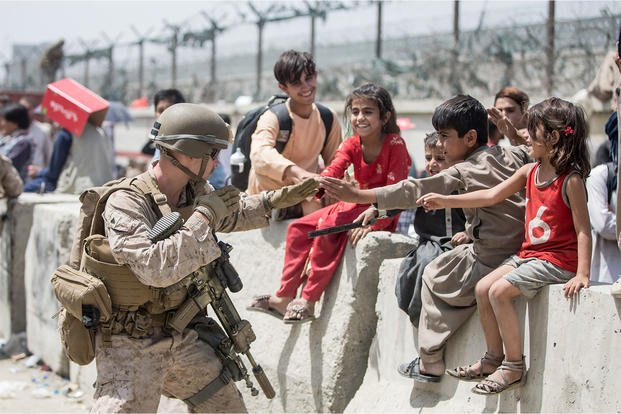 A U.S. Marine Corps Marine with Special Purpose MAGTF - Crisis Response - Central Command plays with children at Hamid Karzai International Airport in Kabul, Afghanistan.