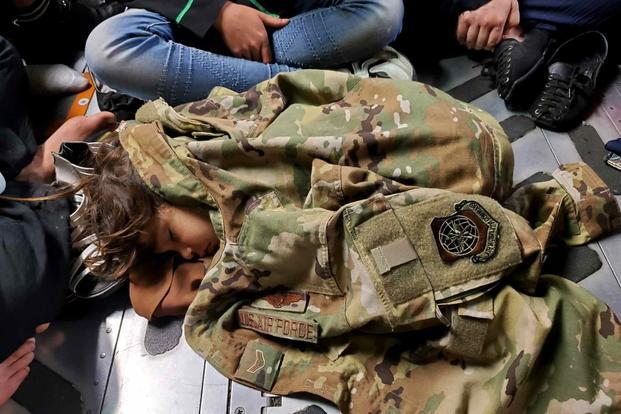 An Afghan child sleeps on the cargo floor of a U.S. Air Force C-17