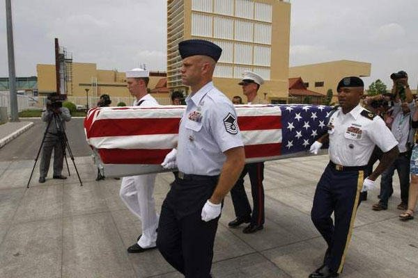 Four U.S. servicemen carry a flag-draped coffin which contains possible remains of a U.S. serviceman during a repatriation ceremony at Phnom Penh International Airport, Cambodia. (Heng Sinith / AP)