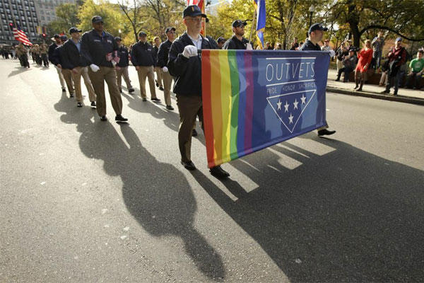 United States Army veteran Ian Ryan, of Dennis, Mass., front, assists in holding an OutVets banner while marching with at a Veterans Day parade, Tuesday, Nov. 11, 2014, in Boston. (AP Photo/Steven Senne)