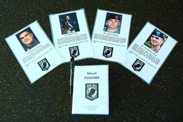 Photo cards at the peak of Mount POW/MIA near Anchorage, Alaska honor several soldiers who have been award the POW Medal (Photo: courtesy of Kirk Alkire)