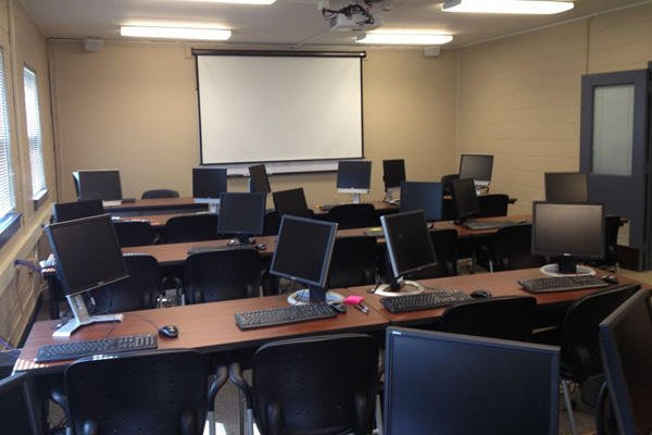 Empty classroom computer screens.