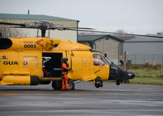 A Coast Guard MH-60 Jayhawk helicopter with a special yellow paint scheme lands at Coast Guard Air Station Astoria, Ore., Jan. 15, 2016. (Coast Guard/Jonathan Klingenberg)