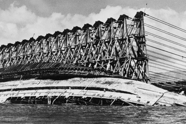 The capsized battleship USS Oklahoma is salvaged at the Pearl Harbor naval base in 1943. An Omaha forensic lab is working to identify the remains of sailors who died on board. (US Navy photo)