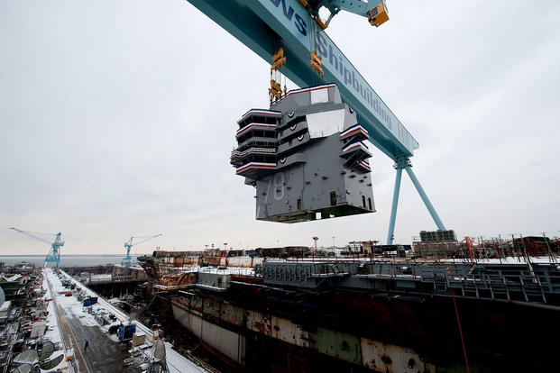 "The Gerald R. Ford's ""island"" -- weighing 555 metric tons -- is lowered onto the aircraft carrier's deck on Jan. 26, 2013 at Newport News Shipbuilding in Virgina. (US Navy photo)"