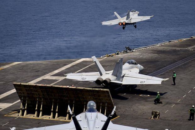 "F/A-18F Super Hornets, from the ""Black Knights"" of Strike Fighter Squadron (VFA) 154, launch from the flight deck of the USS Nimitz (CVN 68) in the Arabian Gulf, July 29. (US Navy photo/Weston Mohr)"