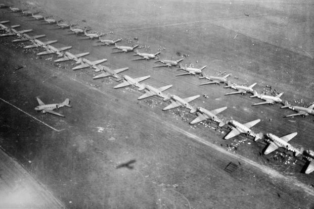 Long, twin lines of C-47 transport planes are loaded with men and equipment at an airfield from which they took off for Holland September 17, 1944. The C-47's carried paratroopers of the First Allied Airborne Army. (Photo: National Archives)