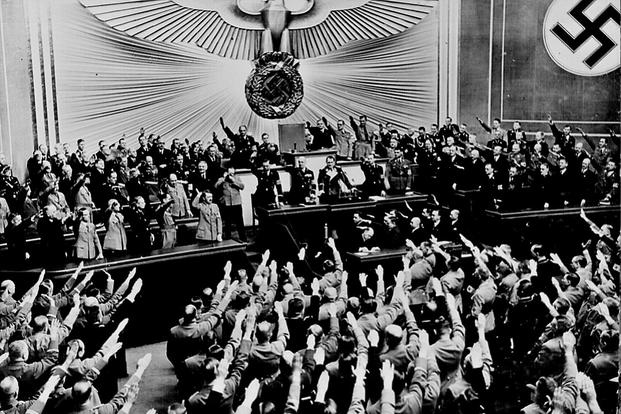 "Adolf Hitler accepts the ovation of the Reichstag after announcing the ""peaceful"" acquisition of Austria in  March 1938. (National Archives photo)"