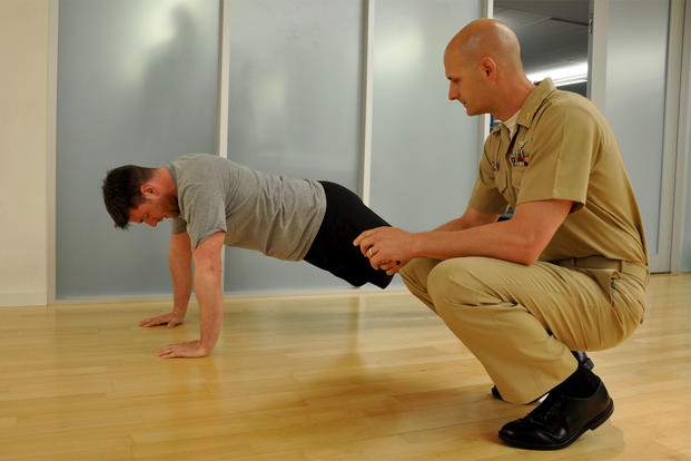 Lt. Neil Cascardo, Medical Service Corps personnel planner, administers the push-up portion of the Navy Physical Readiness test to Paul Ross, BUMED deputy public affairs officer. (Photo by Valerie Kremer)