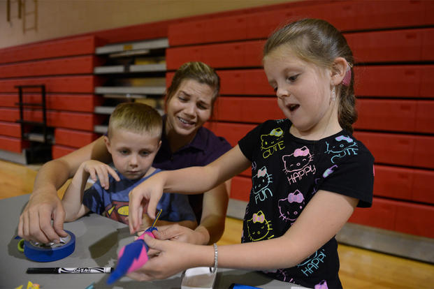 A girl  makes a rocket out of construction paper with her mother and brother during the Child Find Clinic and Community Resource Awareness Fair at Shaw Air Force Base, S.C., Aug. 14, 2013. (Jeffers/Released)