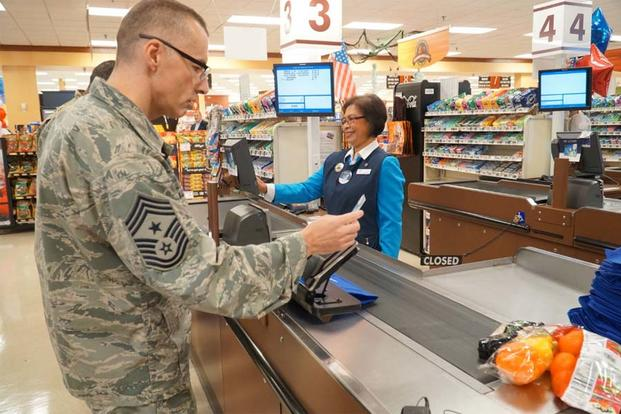 Chief Master Sgt. Stuart Allison, DeCA senior enlisted advisor, was the first to swipe a MILITARY STAR card at the commissary during a rollout ceremony at Oct. 5 at Fort Lee. (Army Photo)