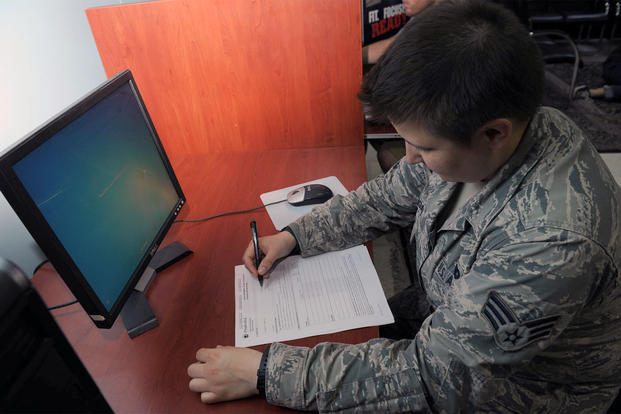 An ariman fills out an SGLI form (Photo: AFNS.)