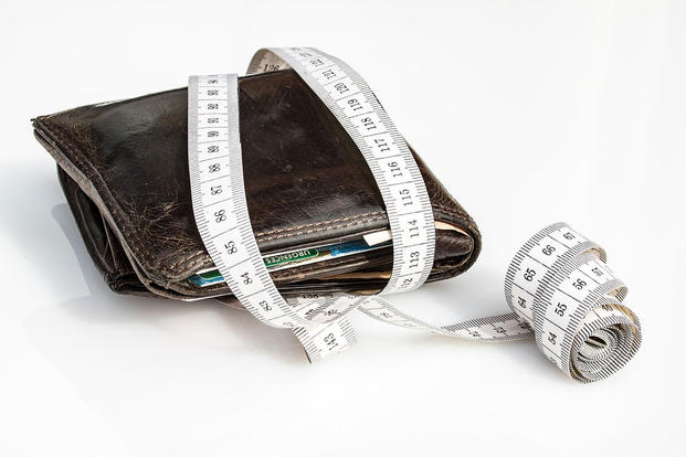 A tape measure measuring a wallet